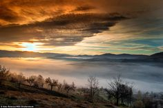 A dense covering of fog obscures nearly the entire valley below in this image of the Trans...