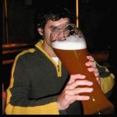 Rapaz tomando um copo gigante de cerveja