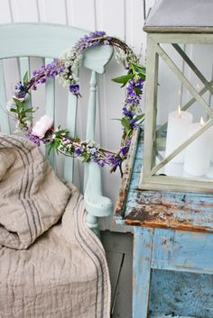 Front porch with purple heart branch wreath, painted blue chair, outdoor blanket, side table, and lantern
