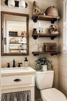 There's many places to find antique and rustic decor items. Try a local thrift store and search for a rustic mirror. This gold one pops out against the neutral decor in this bathroom and makes it interesting.