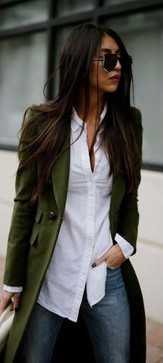 Chic olive coat with white shirt and blue jeans.