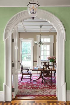 An arch trimmed out in ornate Greek Revival casing invites the eye through a dining room and beyond.