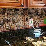 Garden Stones: Square tiles of stones are used (purchased) and applied to the backsplash wall with tile setting mat from the hardware store, grout is used to fill in all the spaces between the stones.