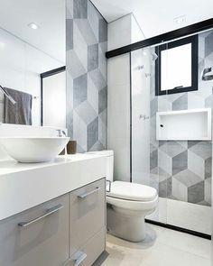 This contemporary bathroom features various key trends including a countertop basin, grey furniture and geometric wall patterns.