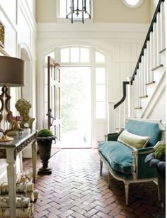 I adore the chevron brick flooring, the front door and all the white paneling.