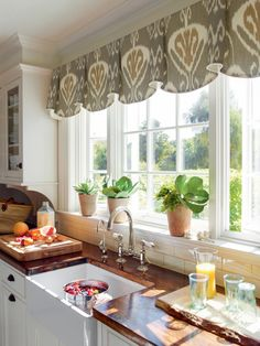 "In a kitchen with simple style and a mostly white color palette, a splash of pattern can add personality. ""Help frame a beautiful view with a valance mounted above the window. This ikat-patterned fabric, Bansuri in Slate, has a rich neutral that adds interest to the solid white cabinets,"" says the manufacturer."