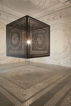 Laser-cut wood cube projects beautiful shadow patterns onto surrounding gallery walls. By Anila Quayyum Agha.