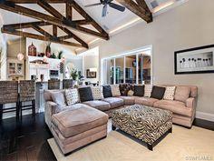 Transitional family room - exposed beams - tan and zebra - safari house.  Pelican Bay in Naples, FL