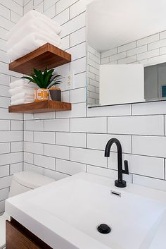 Simple small white NYC bathroom with white subway tile and bathroom shelving mounted on the wall to save space. Small Bathroom Shelves, Small White Bathrooms, Kitchen And Bath Remodeling, Bathroom Renovations, White Subway Tile Bathroom, Subway Tiles, Modern Southwest Decor, City Bathrooms, Bathroom Interior