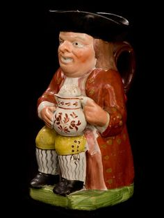"TOBY JUG MAN IN RED COAT    19TH CEN TOBY JUG MAN IN RED COAT WITH DECORATE TANKROD AND LARGE ALE CIRCA 1840  9 3/8"" H"