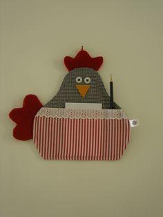 Porta recado em tecido estruturado com manta específica para patchwork no formato de galinha. Crista e rabo feitos em feltro. Com um bolsinho para colocar o bloquinho e dois bolsinhos para lápis e caneta.    ** Bloquinho e 1 lápis acompanham o produto  ** Medida aproximada: 26cm largura X 24,5cm altura R$ 22,00