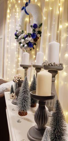 Karácsonyi esküvőnél mindenképp érdemes a koszorút, mint dekorációs elemet használni. Ha modern hangulatra vágysz, nem a klasszikus piros -zöld, vagy arany árnyalatokra, akkor válaszd a a szürkét és a fehéret. A fényfüggöny még karácsonyosabbá teszi a látványt. A koszorúra pedig tehetsz néhány hangsúlyosabb színű, jelen esetben királykék gömböt.