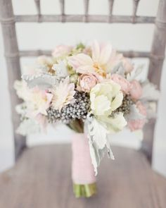 The bridesmaids' bouquets included dahlias, spray roses, dusty miller, gray brunia berries, white hydrangea, and peegee hydrangea.