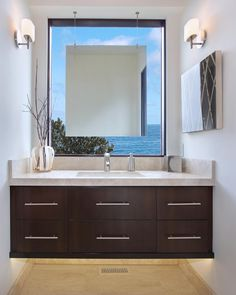 A floating vanity tucked into a window niche creates a spectacular focal point in this contemporary California guest bathroom. A suspended mirror is framed by a breathtaking view of the Pacific Ocean. Accent lighting beneath the vanity adds to the room's dreamy feel.