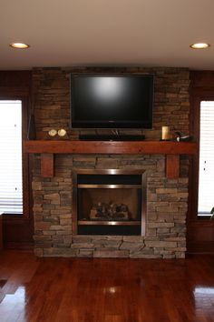 Beautiful Stone fireplace with wood mantle and floor