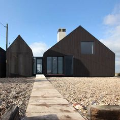 The Shingle House byNORD Architecture is the second completed holiday home inAlain de Botton'sLiving Architecture project. Located on a beach in Dungeness, Kent, the house is clad in tarred black shingles. The interior is clad in white-painted wooden panels. Glazedconcertinadoors in the living areas and bedrooms open up the interior spaces to the beach. The