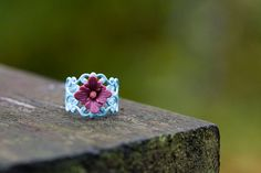 Resin flower in dark raspberry - Blue filigree ring is adjustable.   View more items in my shop: http://www.etsy.com/shop/SilentRoses Please read shop policies before purchasing: http://www.etsy.com/shop/SilentRoses/policy If you dont find your country in the ship to list, please contact me. :)   Thanks for stopping by.