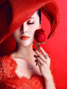 asian woman in red hat holding a single red rose