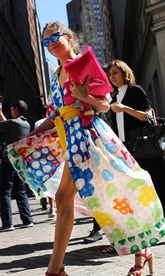 A floral dress with a yellow belt and neon clutch