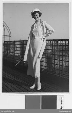 1933. Modell i studentklänning, kappa, pumps och studentmössa. Foto: Erik Holmén för Nordiska Kompaniet
