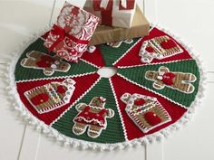 Create your own crochet Christmas tree skirt for an handmade accessory under the tree. The festive Gingerbread Tree Skirt, designed by Donna Collinsworth, features an adorable scene with gingerbread boys, girls and houses set on alternating wedges of red and green. A wide lace border accents the outside edge of the skirt to give an impression of icing. This tree skirt is full of sweetness with completely decorated gingerbread just waiting to be covered with presents. A slit along one wedge