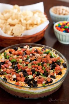 A classic 7 layer bean dip made by layering refried beans creamy guacamole spi 7 Layer Bean Dip, Layered Bean Dip, 7 Layer Taco Dip, 7 Layer Mexican Dip, Mexican Bean Dip, 7 Layer Dip Recipe, Appetizers For Party, Appetizer Recipes, Delicious Appetizers