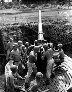 A U.S. Army anti-aircraft gun crew man a three-inch M3 anti-aircraft gun at Girua Airport during the Battle of Buna–Gona, photographed by John A. Moore (December 17, 1942). The battle began on November 16, 1942, when Australian and U.S. forces attacked the main Japanese-held beachheads in New Guinea at Buna, Sanananda and Gona near Dobodura in Oro Province, Territory of Papua (now Papua New Guinea).