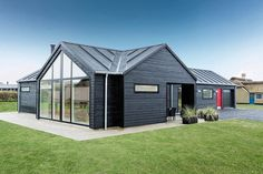 Contemporary black exterior of the summer home with a bright red door Scandinavian Beauty: Exquisite Summer House Epitomizes Minimal Danish Design