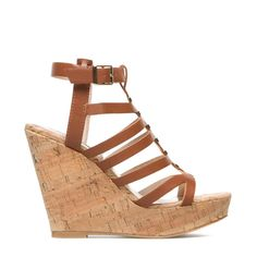 85d8a44a5aa Indyanna s cage styling and opulent metallic accents rest on a towering  cork-effect platform wedge.
