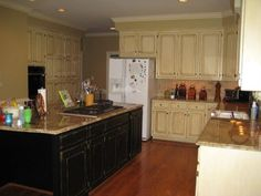 Rustic glaze cabinets with black and almond distressed island.