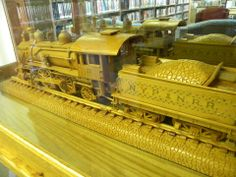 A donation by Grover LeCates, who hand-carved the engine, car, and tracks. One of 4 models, all handmade by Mr. LeCates, on display in the Library.