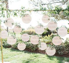diy mariage plan de table en cercles de papier avec noms invités écrits dessus, calligraphie, un cadre doré avec des plantes enroulées autour