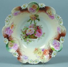 "RS Prussia Bowl, 11""d.; Mold 37a, ""Shield "" varian, FD 44, basket full of chrysanthemums in center on white with cream walls, brown accents at ""shields"", blue green accents to ""Shields"" each with 2 chrysanthemums of pink or yellow, green, pink, white and orange chrysanthemums around below rim and natural colored daisies on rim, gold highlights to mold details"