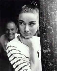 Audrey Hepburn, wearing a tight bun and stripes.