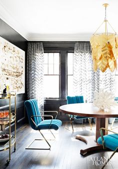 Dark dining room walls with modern sea blue chairs and gold leaf pendant fixture.