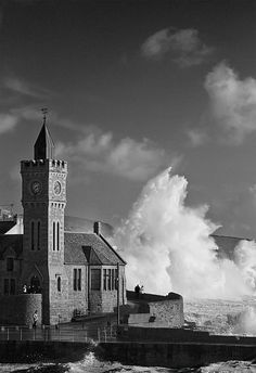 The Institute in Porthleven, Cornwall with rough seas pounding the coastline.
