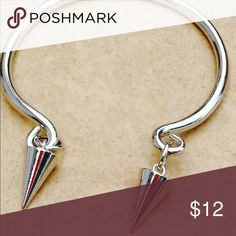 Silver Tone Open Cuff Spike Charm Bangle Silver tone polished finish open cuff bracelet features a dangling spike charm from each end.  A fun, funky and unique design.  Spike measures 5/8 inch long x 1/4 inch wide.  Open cuff is one size fits most. Jewelry Bracelets