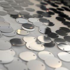 Paiete rotunde argintii de 18 mm pe tul alb KX1823.  Latime (cm) 130 / 132; Diametru Paieta 18 mm;  Compozitie tul (%) Poliester 100%;