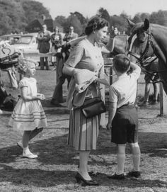 Queen Elizabeth II and her children, Princess Anne and Prince Charles, wait together for the next event in the Braemar Highland Games, Scotland, September 9th 1957.