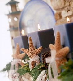 candles decorated with starfish, greens and pine cones.