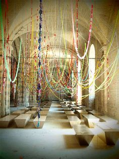 Displayed at the Kiev Biennale, the Choi Jeong Hwa 'Cosmos' installation is a vibrant and expansive interactive sculpture. Visitors are invited to take a seat under the colorful streamers that hang throughout the cathedral hallway. Using a series of playful plastic balls, handmade flowers and playground-esque chains, the installation brings back memories of birthday streamers and holiday garland. The large-scale piece is a complex web of differing textures, colors and materials.