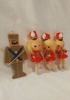 These adorable 1960s Soldier Ornaments have the perfect touch of nostalgia for your Christmas tree! This set includes three puppet soldier girls who each have their own red marching outfit and unique pose. Plus this set comes with an extra flat, woven soldier man with gold accents. Hang these ornaments on your tree or surprise a loved one with happy memories this holiday!  Each soldier girl measures about 5 1/2 tall  * Some wear on all, the soldier girls need cleaning, and the soldier ma...