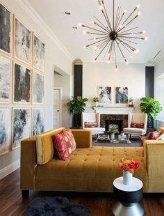 Accent wall framed photo collage | Modern star burst brass light fixture | Mustard yellow open tufted velvet sofa