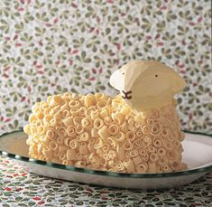 Here is the most adorable lamb cake. Her fleece is made of white chocolate curls.