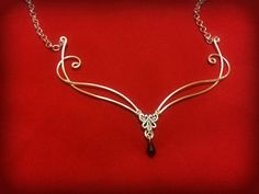 This Elven inspired stunning necklace is handmade from silver plated metal measuring at approximately 5 inches wide this beautiful piece will set off any outfit At the front is a Celtic design made with a deep red siam swarovski elements crystal drop. (see my other listings for the
