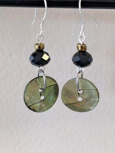 These earrings are made from new vintage buttons and recycled glass beads. Jump rings are made of stainless steel and the ear hooks are made of sterling silver.