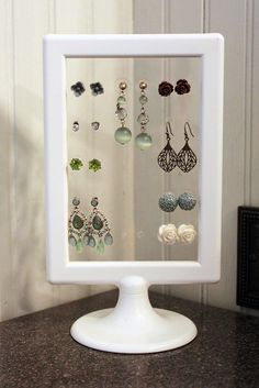 Love this earring stand made from a $1 IKEA frame!! The frame came with 2 pieces of plastic in it, which the creator punched holes in, making it perfect for any type of earring!!