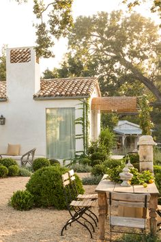 Backyard with gravel, dining area, and fire pit at Patina Farm (a serene modern farmhouse) in Ojai, California by Giannetti Home.