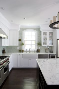 A farmhouse sink, carrera marble countertops, beautiful wood floors and a crackle ceramic subway tile backsplash. What's not to love about this kitchen renovation?