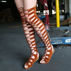 """Get a celebrity inspired ensemble with the Tie Up Thigh High Gladiator Sandals! These boho inspired sandals feature an open toe, lace up pattern, faux suede upper, and full back zipper. Finished with a slightly cushioned insole  and a .25"""" flat heel approx. Top off the look with a floppy sun hat and oversized shades!"""